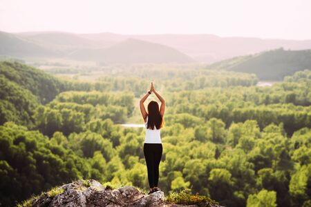 Attractive woman doing yoga. Healthy lifestyle. The concentration of the body. Woman doing yoga in the mountains. Girl doing yoga at sunset. Woman meditates in nature. Meditation in the mountains 版權商用圖片