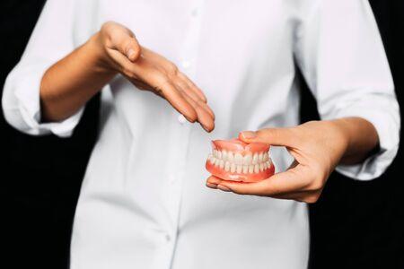 Le dentiste tient des prothèses dentaires dans ses mains. Prothèse dentaire entre les mains du médecin en gros plan. Vue de face de la prothèse complète. Photo conceptuelle de dentisterie. Dentisterie prothétique. Fausses dents