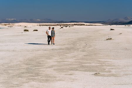 A loving couple walks along the coast of lake Salda in Turkey. Couple travels in Turkey. Lake Salda in Turkey. A lonely pair. Happy couple walking on empty sandy beach. Beautiful couple in nature