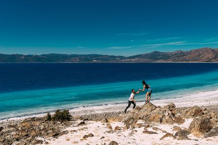 Man and woman have fun on the beach. Man and woman on the coast in Turkey. Couple on vacation. Honeymoon trip. Lovers at the lake in the mountains. Couple travels in Turkey. Lake Salda in Turkey 版權商用圖片