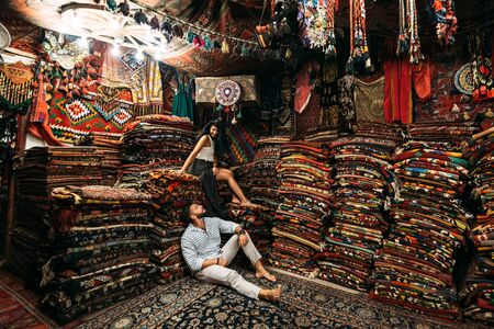 Young couple walking in Cappadocia. Man and woman in the store. Couple in love in Turkey. Man and woman in the Eastern country. Happy couple travels the world. Persian shop. Tourists in store