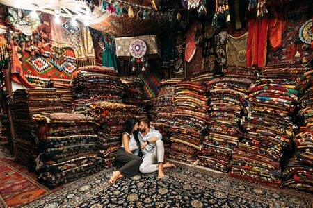 Young couple walking in Cappadocia. Man and woman in the store. Couple in love in Turkey. Man and woman in the Eastern country. Happy couple travels the world. Room with carpets. Tourists in store