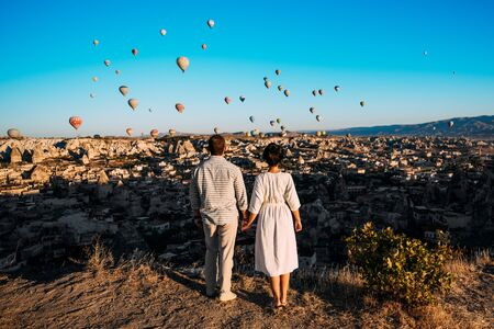 Hot air balloon flying over spectacular Cappadocia - couple watching hot air balloons at the hill of Cappadocia. Couple standing by each other in Turkey Cappadocia with hot air balloons at sunrise.