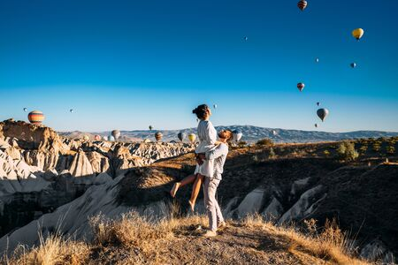 A couple in love in Cappadocia. The couple travels the world. Vacation in Turkey. Honeymoon in Cappadocia. Happy couple traveling. Honeymoon trip. Hot air balloon flights. Woman in the arms of a man 版權商用圖片