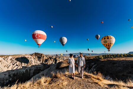 Couple in love stands on background of balloons in Cappadocia. The couple travels the world. Vacation in Turkey. Honeymoon trip. Hot air balloon flights. Happy young couple meets dawn in Cappadocia