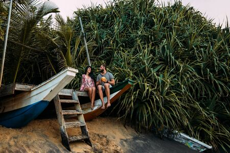 A Couple in love on the seaside drinking coconut.