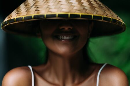 Portrait of a beautiful girl in an Asian conical hat. Portrait of a smiling girl. Beautiful smile. Close-up smile. Funny girl. Smiling girl. Funny portrait. A woman in a Balinese conical hat. Banco de Imagens