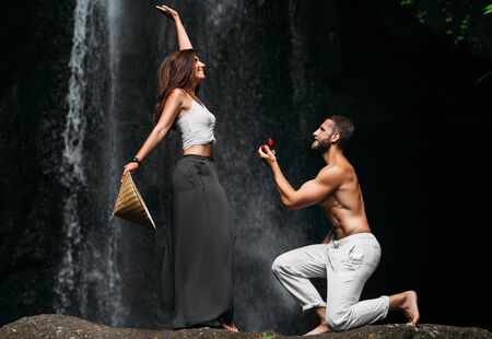 A man proposes to a woman at a waterfall. A guy proposes to a girl in Bali. Offer of a hand in travel. Honeymoon trip. Declaration of love. A couple in love on a waterfall. Happy couple in bali
