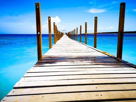 Ein Foto der Natur, aufgenommen mit einem Smartphone. Pier geht ins blaue Meer. Schöne Bootsanlegestelle in Bali. Der Pier relativiert sich vor dem Hintergrund des Meeres und des blauen Himmels. Standard-Bild