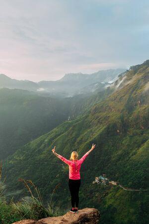 Woman meets sunrise in the mountains. Girl traveling to Sri Lanka. Mountain sports. Athlete happy finish. Mountain tourism. Walking tour. The journey to the mountains. Crossfit in the mountains