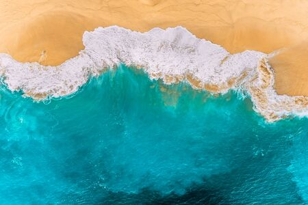 Aerial view of turquoise ocean waves in Kelingking beach, Nusa penida Island in Bali, Indonesia. Beautiful sandy beach with turquoise sea. Splashing ocean waves reach sandy beach. Beaches of Indonesia Banque d'images