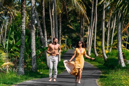 Beautiful couple running among palm trees in Bali, Indonesia. Honeymoon on the Islands. A happy couple in love runs along the road. Honeymoon trip. Wedding trip. Couple on vacation in Bali Banque d'images - 141753146