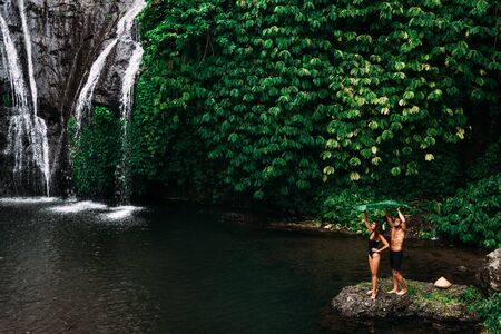 A couple in love at a waterfall in Indonesia. A couple in love in the tropics. Beautiful couple traveling on the island of Bali. Man and woman on the background of nature. Copy space
