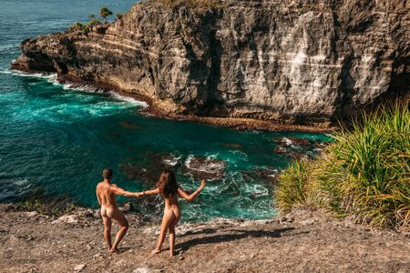Nude couple on the beach in Indonesia. Naked couple on an empty beach. Naked couple by the sea. Happy couple on vacation. Honeymoon trip. A man and a woman without clothes on the beach. Copy space