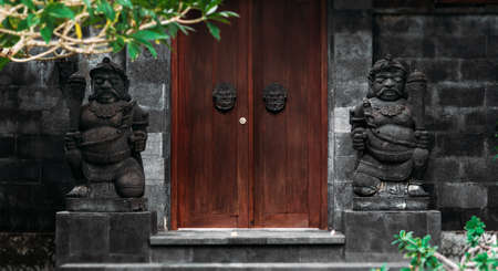 Door or gate to enter into traditional balinese garden architecture detail. Wooden Indonesian gate guarded by stone statues. Old wooden door, entrance to traditional Hindu temple on Bali, Indonesia