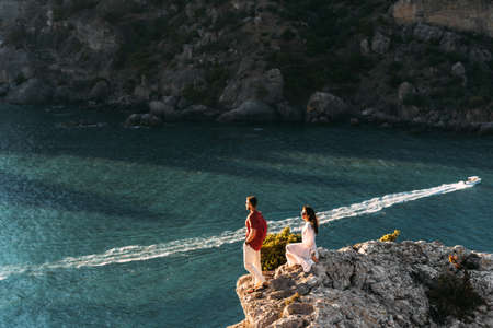Couple in love at dawn by the sea. Honeymoon trip. Man and woman meet the sunset by the sea. Man and woman traveling. Wedding travel. Holiday romance. Beautiful couple by the sea. Copy space