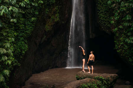 Beautiful couple at the waterfall. A couple in love travels to Indonesia on the island of Bali. A man and a woman at a waterfall in Indonesia. Vacation in Bali. Honeymoon trip. Copy space