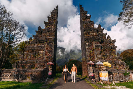 Beautiful couple at the Baltic temple. Man and woman traveling in Indonesia. Couple at the Bali gate. The couple travels the world. Travel to tourist places in Asia. Tourists in Bali. Copy space.