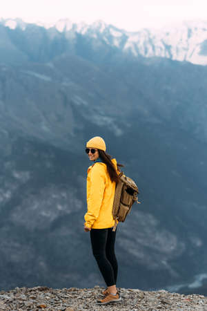 A young woman in Hiking gear stands against the backdrop of mountains and looks at the camera. A woman among the mountains. Traveling woman with a backpack on the background of mountains. Copy space