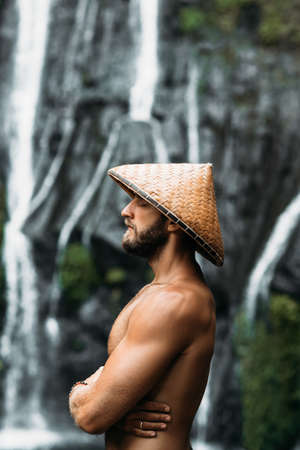 Portrait of a sports guy in an Asian conical hat. Portrait of a man in profile. Portrait of a bearded man. A man meditates in a Balinese conical hat. Beautiful male portrait. A man symbolizing calm 版權商用圖片
