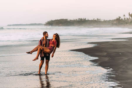 Loving couple on the beach having fun. Honeymoon of newlyweds. Couple travels. Holiday in GOA. Lovers on the island. Couple fooling around on the sea. Guy and girl hugging at sea. Copy space