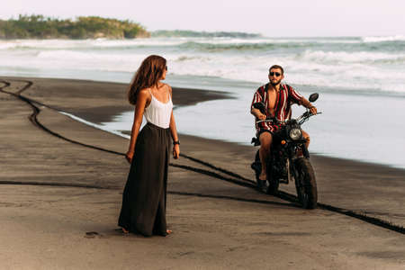 Couple on a motorbike on the beach. A couple in love on the beach meets the sunset. Beautiful couple on a motorbike. Travel on a motorbike. Lovers on the beach. Journey to the island of bali