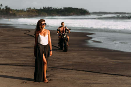 Stylish couple on a motorbike on the beach. A couple on a motorbik meets the sunset. Beautiful couple on a motorbike. Travel on a motorbike. Lovers at sunset. Journey to the island of Bali. Copy space