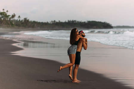 A man and a woman have fun at sunset by the sea. Happy couple on the beach. Tanned couple having fun at sunset by the sea. Wedding trip. A couple on vacation. The couple is traveling. Lovers travel