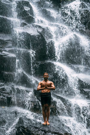 A man does yoga at a waterfall. Healthy lifestyle. The concentration of the body. A man does yoga in Bali. A man meditates in nature. Meditation at the waterfall. Young man practicing yoga. Copy space