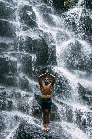 A man of athletic build does yoga. Healthy lifestyle. The concentration of the body. A man does yoga in nature. A man does yoga in Bali. A man meditates in nature. Meditation at the waterfall 版權商用圖片