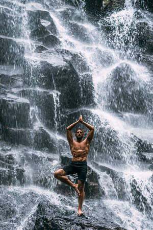A man of athletic build does yoga. Healthy lifestyle. The concentration of the body. A man does yoga at a waterfall. A man does yoga in Bali. A man meditates in nature. Meditation at the waterfall 版權商用圖片
