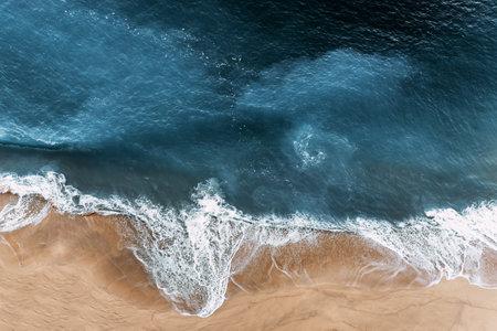Aerial view of the blue ocean waves on the beach. Beautiful sandy beach with blue sea. Lonely sandy beach with beautiful waves. Aerial view of blue ocean waves in Kelingking beach, Nusa penida 版權商用圖片