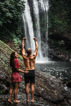 Couple at the waterfall, rear view. Honeymoon trip. Couple on vacation in Bali. A couple in love travels the world. Vacation on the island of Bali. Happy couple close up. Tourists at the waterfall