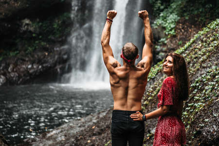 Lovers at the waterfall, rear view. Couple admiring a beautiful waterfall in Indonesia. Couple on vacation in Bali. Honeymoon trip. The couple is traveling in Asia. Vacation on the island of Bali