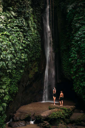 Lovers at the waterfall. Couple admiring a beautiful waterfall in Indonesia. Couple on vacation in Bali. Honeymoon trip. The couple is traveling in Asia. Vacation on the island of Bali with copy space 版權商用圖片