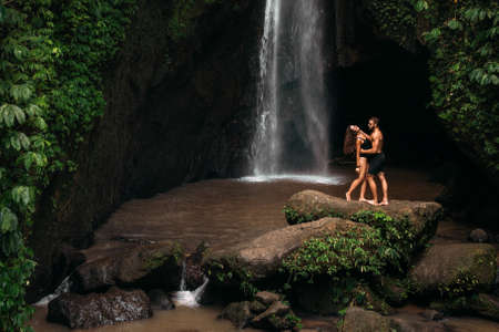 Lovers at the waterfall. Couple admiring a beautiful waterfall in Indonesia. Couple on vacation in Bali. Honeymoon trip. The couple is traveling in Asia. Vacation in Bali. Copying a space