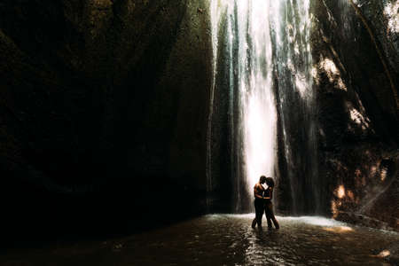 Beautiful couple in a cave with a waterfall. Athletic man and woman under the streams of a waterfall. A couple under a tropical waterfall in twilight light. Tukad Chepung Waterfall. Copy space