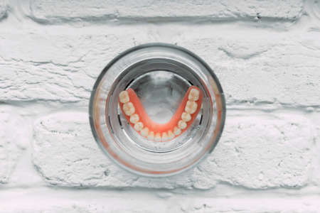 A denture in a glass of water. Dental prosthesis care. Full removable plastic denture of the jaws. Acrylic denture. Lower jaw with false teeth. Dentures or false teeth, close-up. 版權商用圖片