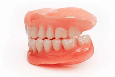 Full removable plastic denture of the jaws. Set of dentures on a white background. Two acrylic dentures. Upper and lower jaws with fake teeth. Dentures or false teeth, close-up.