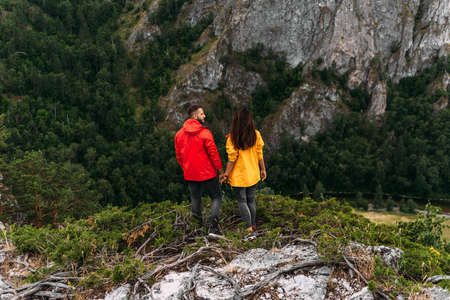 A couple in love on a rock admires the beautiful views, rear view. A man and a woman on a rock. A couple in love travels. A walk in the mountains. Couple traveling through the mountains. Hiking