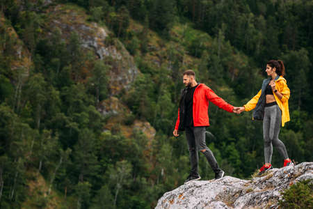 A couple in love on a rock admires the beautiful views. A man and a woman on a rock. A couple in love travels. A man and a woman hold hands. Couple traveling through the mountains. Copy space