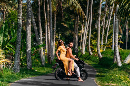 A happy young couple rides a scooter among the palm trees. A beautiful young couple is traveling on a scooter in Sri Lanka. Cheerful couple riding scooter at countryside road, vacation concept. 版權商用圖片