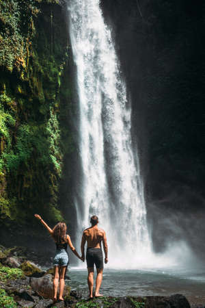 Couple at the waterfall, rear view. Couple on vacation in Bali. Honeymoon trip. A couple in love travels the world. Vacation on the island of Bali. Tourists in Bali. Copy space 版權商用圖片
