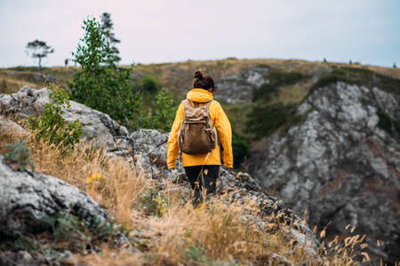 Mountain traveler, rear view. Mountain sports. Mountain tourism. Walking tour. The journey to the mountains. Traveling woman with a backpack on the background of mountains, rear view. Copy space 版權商用圖片