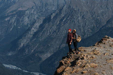 A couple in love on a rock admires the beautiful views. A man and a woman on a rock. A couple in love travels. A man and a woman in the Caucasus mountains. Couple traveling through the mountains 版權商用圖片