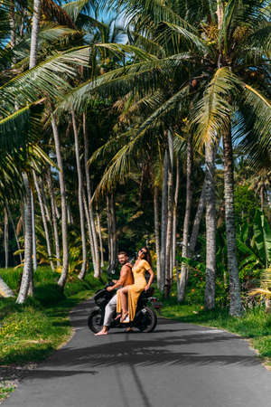 A couple in love on a scooter among the palm trees. Happy couple on vacation in Bali. The couple travels the world. Vacation in Asia. Traveling on a scooter in Bali. Honeymoon trip. Vacation in Bali