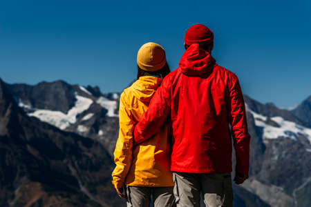 People in colorful jackets on the background of the mountains, rear view. An active couple is engaged in Hiking. A young couple is engaged in tracking. Hiking. People in the mountains