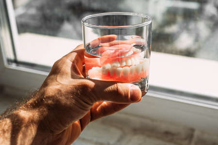 A denture in a glass of water. Dental prosthesis care. Full removable plastic denture of the jaws. Two acrylic dentures. Upper and lower jaws with fake teeth. Dentures or false teeth, close-up.
