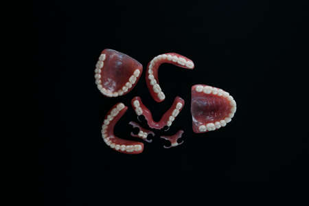 Dentures on a black background. Close-up of dentures. Dentistry is conceptual photography. Prosthetic dentistry. False teeth. Prosthetics. Close-up of plastic dentures. Teeth on a black background 版權商用圖片