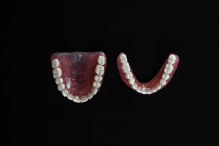 Full removable plastic denture of the jaws. A set of dentures on a black background. Two acrylic dentures. Upper and lower jaws with fake teeth. Dentures or false teeth, close-up. Copy space 版權商用圖片
